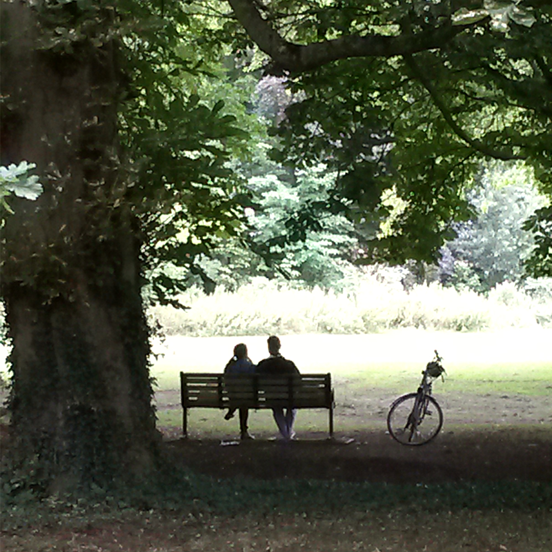 A couple sat on a park bench in an open space in Cambridge.